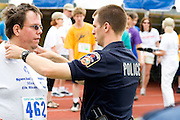 Policeman placing award ribbon on proud athlete. Special Olympics U of M Bierman Athletic Complex. Minneapolis Minnesota USA