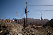 A forest of telephone poles in the dry mountains of Golok region, Tibet (Qinghai, China).