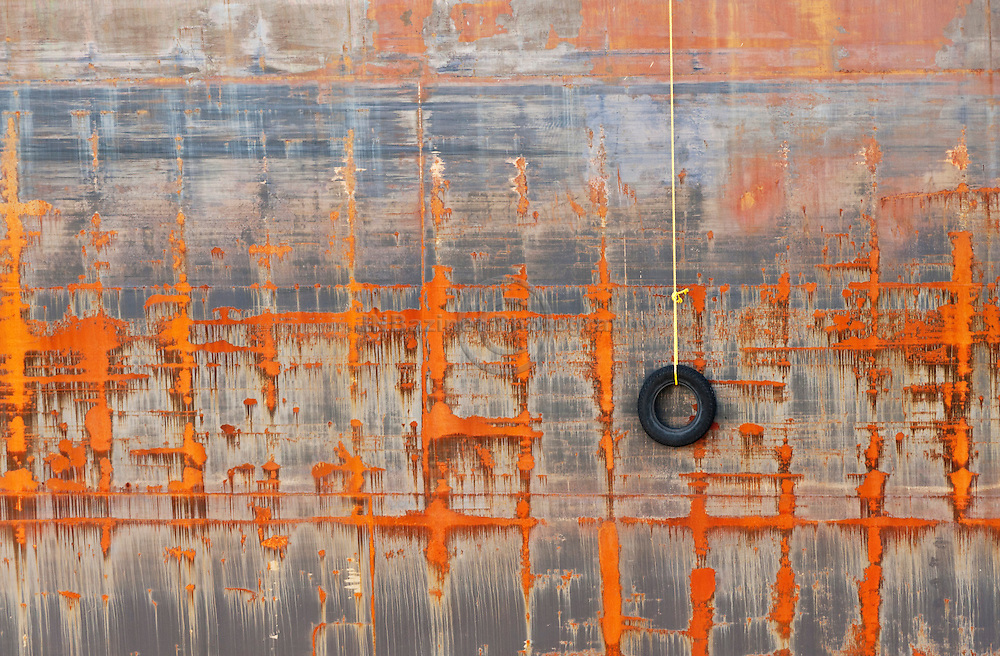 Abstract rows and columns of rust on the side of shipping vessel whose small recycled tire has been ineffective in protecting the ship.