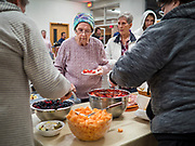 """26 FEBRUARY 2020 - FARMINGTON, MINNESOTA: DIANE WILLIAMS, from Farmington, gets a salad at the community dinner at Faith Church, a United Methodist Church in Farmington, MN, about 30 minutes south of the Twin Cities. She said she used to shop for groceries at the now closed grocery store in Farmington, but now someone has to bring her groceries to her from store in Lakeville. The dinner is sponsored by Loaves & Fishes, a Christian organization that provides food for community dinners and foodbanks. Farmington, with a population of 21,000, is a farming community that has become a Twin Cities suburb. The city lost its only grocery store, a Family Fresh Market, in December, 2019. The closing turned the town into a """"food desert."""" In January, Faith Church started serving the weekly meals as a response to the store's closing. About 125 people per week attend the meal at the church, which is just a few blocks from the closed grocery store. The USDA defines food deserts as having at least 33% or 500 people of a census tract's population in an urban area living 1 mile from a large grocery store or supermarket. Grocery chains Hy-Vee and Aldi both own land in Farmington but they have not said when they plan to build or open stores in the town.      PHOTO BY JACK KURTZ"""
