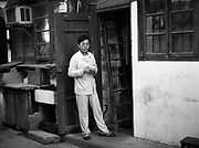 A man eats a bowl of rice in his pajamas in front of his home in an old Shanghai neighborhood.