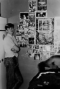 Teenager in bedroom standing next to posters, London, UK, 1983