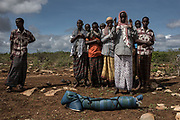 Bashir Bille, 40, stands by the body of his son, Noor Bashir, 4, as men pray prior to his burial at the Mogor I Maanyi IDP camp in Baidoa, Somalia on May 13, 2017. Noor died from complications from cholera, and was the third burial of the morning.