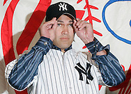 Johnny Damon trys on his new Yankees hat at a press confrence introducing him to the New York Media New York. Friday 23 December 2005 Andrew Gombert for the Boston Globe
