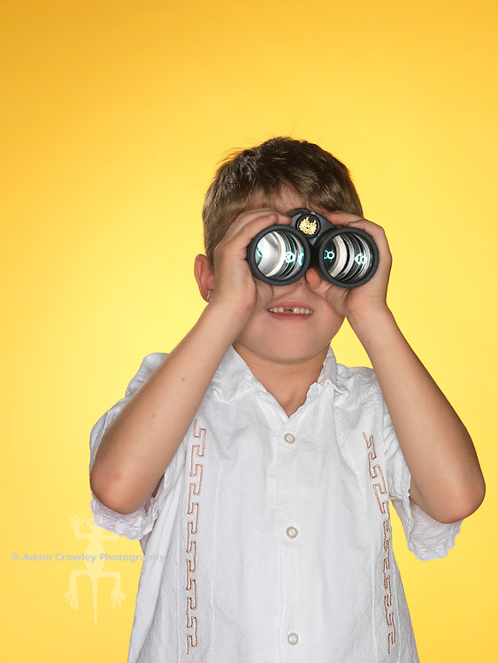 7 year old boy looks through a pair of binoculars.