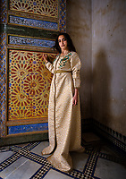 FEZ, MOROCCO - CIRCA MAY 2018:  Young Moroccan woman in traditional dress seating by a Moroccan door in Fez