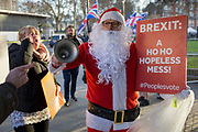 As Prime Minister Theresa May tours European capitals hoping to persuade foreign leaders to accept a new Brexit deal (following her cancellation of a Parliamentary vote), a pro-EU Santa ringing a Brexit bell is taunted by Brexiteers during a protest opposite the Houses of Parliament, on 11th December 2018, in London, England.