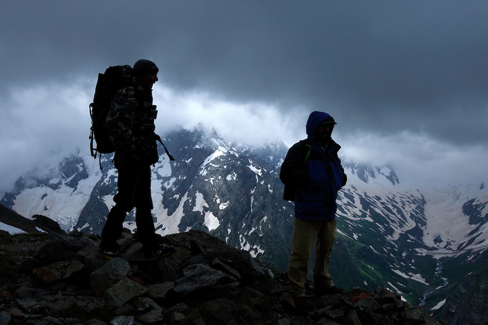 Russia, Caucasus. Teberdinsky biosphere reserve. On Mussa-Achitar Krugozor near Dombay, around 3000 m asl. Persons in silhouettes. Guide and park ranger Zaur Amatovich Takhtiev in picture to left and to right guide Vladimir Yu. Arkipov. Model release form no 1 and 2.