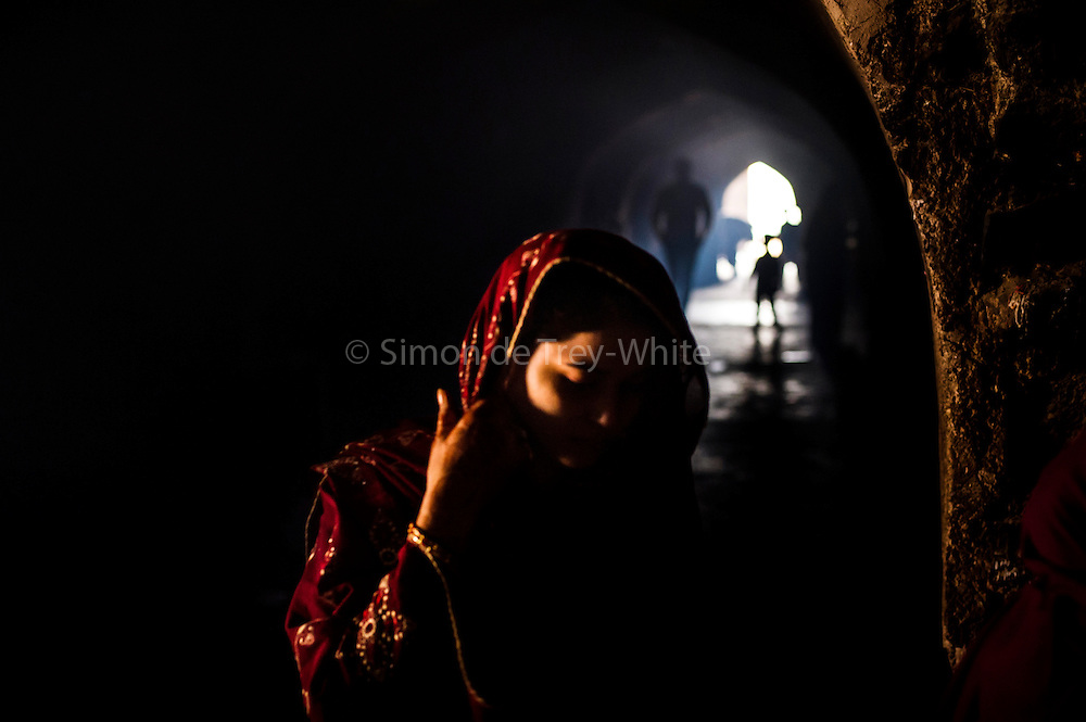 """17th December 2015, New Delhi, India. A woman in the ruins of Feroz Shah Kotla in New Delhi, India on the 17th December 2015<br /> <br /> PHOTOGRAPH BY AND COPYRIGHT OF SIMON DE TREY-WHITE a photographer in delhi<br /> + 91 98103 99809. Email: simon@simondetreywhite.com<br /> <br /> People have been coming to Firoz Shah Kotla to pray to and leave written notes and offerings for Djinns in the hopes of getting wishes granted since the late 1970's. Jinn, jann or djinn are supernatural creatures in Islamic mythology as well as pre-Islamic Arabian mythology. They are mentioned frequently in the Quran  and other Islamic texts and inhabit an unseen world called Djinnestan. In Islamic theology jinn are said to be creatures with free will, made from smokeless fire by Allah as humans were made of clay, among other things. According to the Quran, jinn have free will, and Iblīs abused this freedom in front of Allah by refusing to bow to Adam when Allah ordered angels and jinn to do so. For disobeying Allah, Iblīs was expelled from Paradise and called """"Shayṭān"""" (Satan).They are usually invisible to humans, but humans do appear clearly to jinn, as they can possess them. Like humans, jinn will also be judged on the Day of Judgment and will be sent to Paradise or Hell according to their deeds. Feroz Shah Tughlaq (r. 1351–88), the Sultan of Delhi, established the fortified city of Ferozabad in 1354, as the new capital of the Delhi Sultanate, and included in it the site of the present Feroz Shah Kotla. Kotla literally means fortress or citadel."""