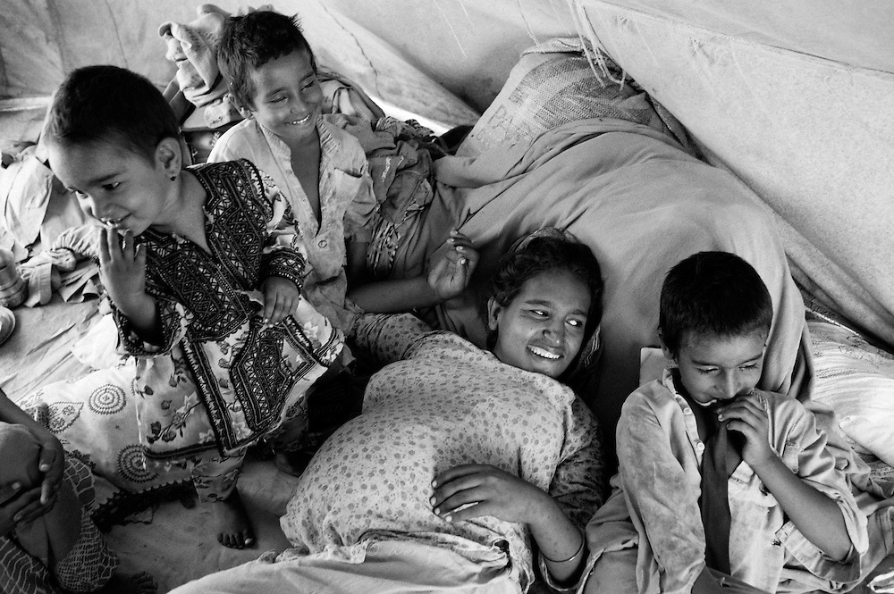 Hamida and her children have fun and laugh. Despite the horrible conditions this family has been living in for the past two months, they still have beautiful moments as a family. Karachi, Pakistan, 2010