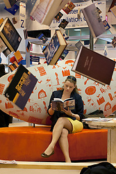 © licensed to London News Pictures. London, UK 16/04/2012. Charlotte Carey from the University of Plymouth Press reads a book at London Book Fair in Earls Court, this noon (16/04/12). It's the largest gathering of the international publishing industry in the UK and one of the largest book fairs in the world. Provides booksellers, publishers and librarians with a concentrated trading and educational platform. Photo credit: Tolga Akmen/LNP