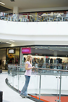 Young woman stands looking over balcony in shopping centre
