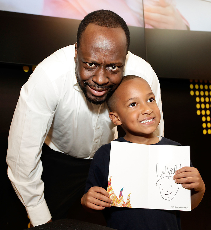 "NEW YORK - MAY 01:  Musician Wyclef Jean poses for a photo with a participant at the Western Union ""Returns the Love"" to Mothers meet and greet at 1440 Broadway on May 1, 2010 in New York City.  (Photo by Joe Kohen/WireImage for Western Union)"