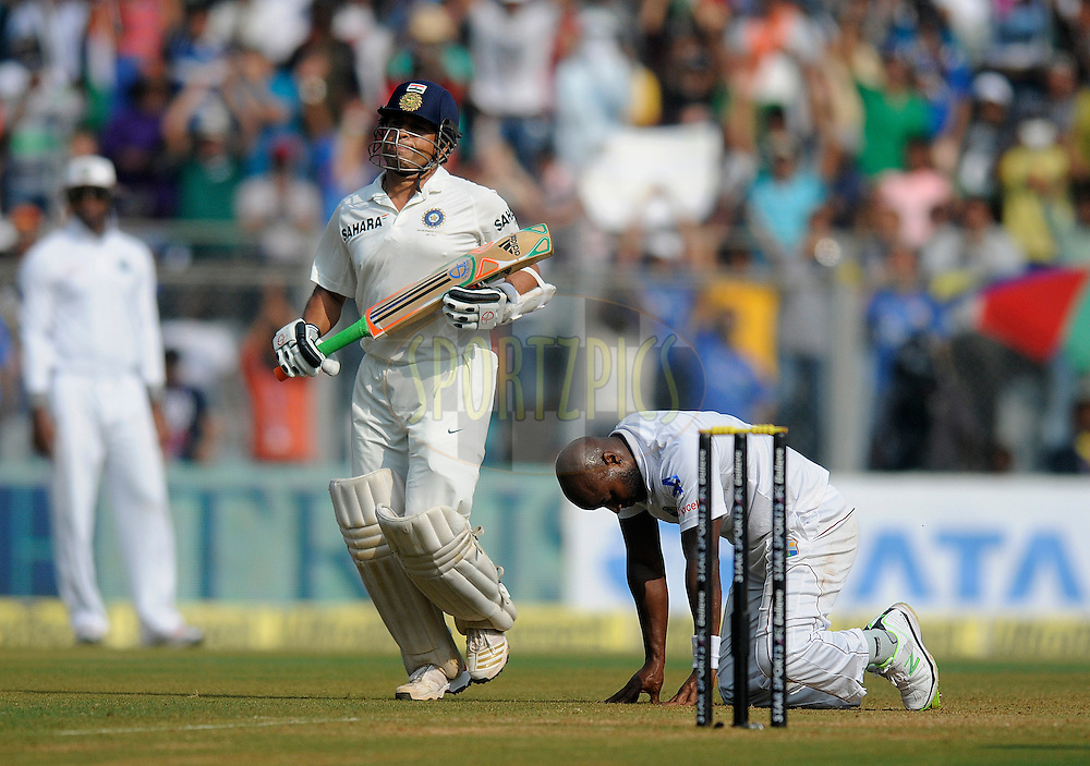 Sachin Tendulkar of India runs for his fifty  runs as Tino Best of West Indies is seen dejected during day two of the second Star Sports test match between India and The West Indies held at The Wankhede Stadium in Mumbai, India on the 15th November 2013<br /> <br /> This test match is the 200th test match for Sachin Tendulkar and his last for India.  After a career spanning more than 24yrs Sachin is retiring from cricket and this test match is his last appearance on the field of play.<br /> <br /> <br /> Photo by: Pal PIllai - BCCI - SPORTZPICS<br /> <br /> Use of this image is subject to the terms and conditions as outlined by the BCCI. These terms can be found by following this link:<br /> <br /> http://sportzpics.photoshelter.com/gallery/BCCI-Image-Terms/G0000ahUVIIEBQ84/C0000whs75.ajndY