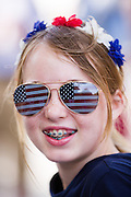 A young girl wearing patriotic flag sunglasses smiles during the I'On neighborhood Independence Day parade July 4, 2015 in Mt Pleasant, South Carolina.
