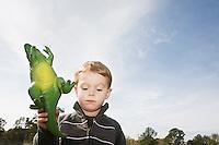 Displeased boy holding toy dinosaur
