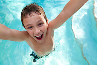 Portrait of kid very playful and jumping in a swimming pool.