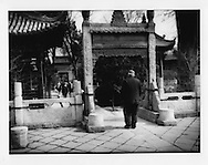 Elders walk through garden of Great Mosque (Daqingzhen Si) of Xian built in Chinese temple style in the 18th century after Friday prayers, Xian, China.  Xian was both China's ancient capital and the terminus of the Silk Road.