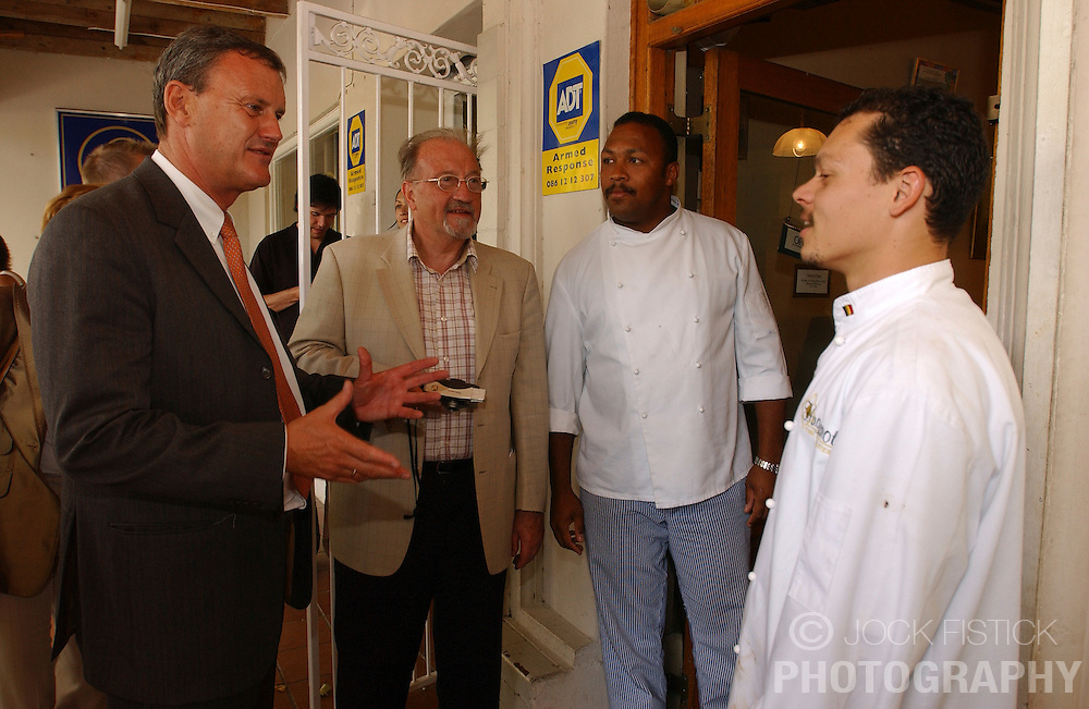 FRANSCHHOEK, SOUTH AFRICA - APRIL-30-2004 - .Marc Verwilghen , Belgian Minister of Development and Cooperation, visits the Huguenot Belgian Chocolate shop in Franschhoek. The shop was established with the help of the Franschhoek Belgian Development Trust and is run by Danny Windvogel and Denver Adonis who were brought to Belgium in 1998 and trained as chocolatiers. Next to the minister is Dr. Jef Velfkiankiers who served in the Belgian Parliament and is now active with the Franschhoek Belgian Development Trust. (PHOTO &copy; JOCK FISTICK)<br />