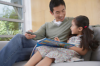 Daughter with picture book sitting side by side on sofa with father