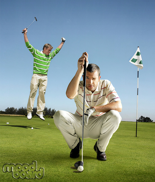 Full length of male golfer jumping with arms raised on putting green