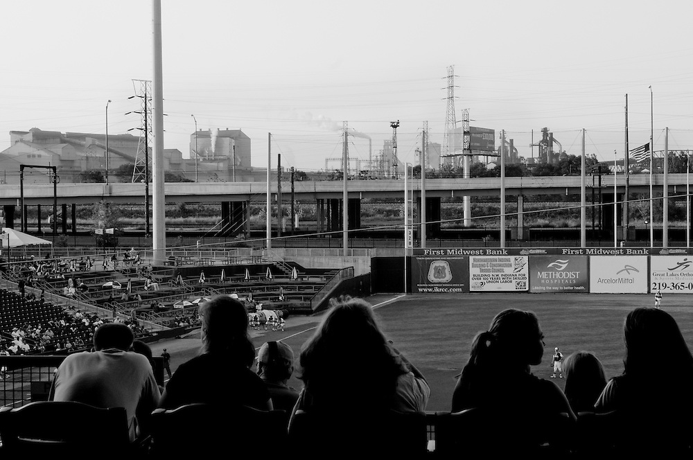 "Spectators at the RailCats, a minor-league baseball team, are pictured against the backdrop of the ""Steel Yard"" stadium and the U.S. Steel plant in Gary, Indiana. The city of roughly 80,000 was founded in 1906 by the U.S. Steel Corporation as the home for its new plant. But in the 1960s Gary's fortunes, so closely linked to the steel industry, took a downturn. Businesses closed and the crime rate spiraled earning Gary the infamous distinction of ""Murder Capital of America."" (© William B. Plowman/Redux)"