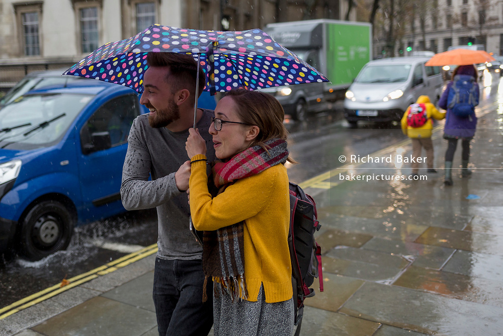 A young man and woman share an umbrella during heavy rainfall on an autumn afternoon in Trafalgar Square, on 24th October 2019, in Westminster, London, England.