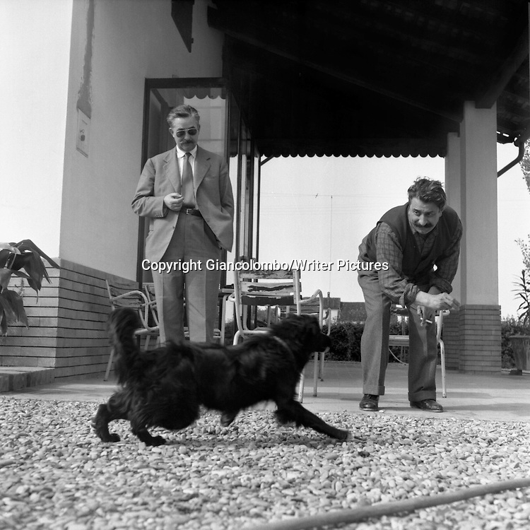Giovannino Guareschi &amp; journalist Carletto Manzoni playing with his dog at his farm. Roncole (Parma), <br /> 1954<br /> <br /> Photograph by Giancolombo/Writer Pictures<br /> <br /> WORLD RIGHTS, NO AGENCY, NO ITALY