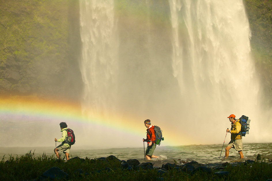 Three backpackers hiking in a stream with a waterfall and rainbow in the background.Hawaii