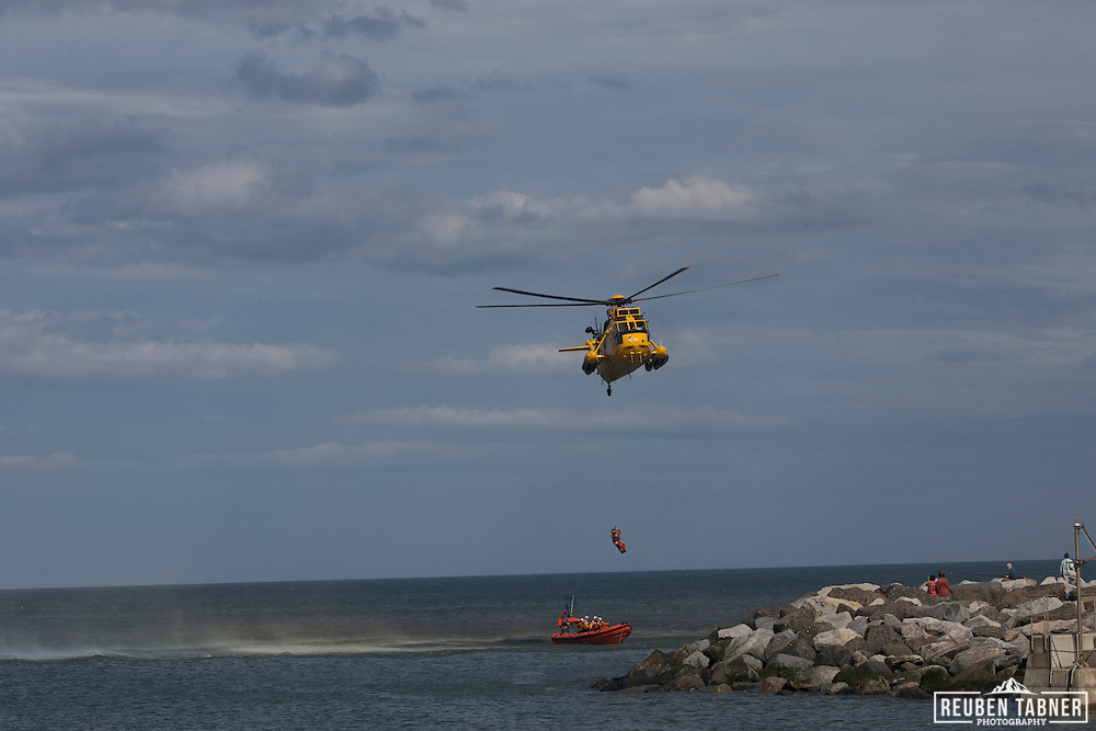 RAF Sea King rescue helicopter, lowers a winchman on to a waiting RNLI inshore lifeboat.