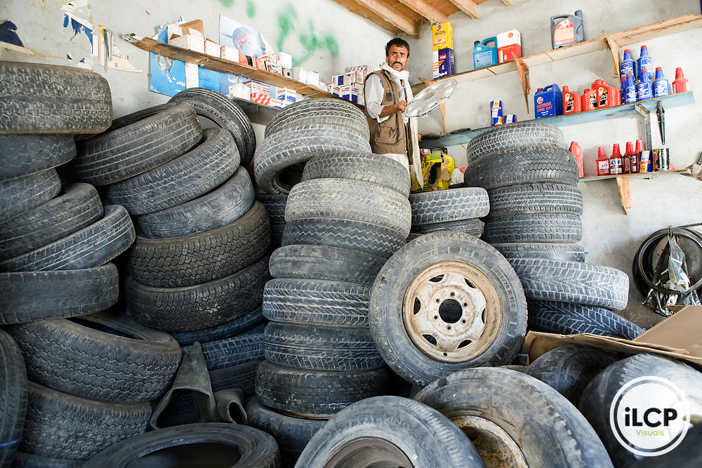 Mechanic standing on spare tires looking for tire hub, Al Ghaydah, Yemen