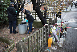 © Licensed to London News Pictures. 02/04/2018. London, UK. Members of a police search team check dustbins in a garden near where floral tributes have been placed in Ellerton Road in Wandsworth, south west London, where 20 year old Devoy Stapleton was stabbed to death at 1am on Sunday 1st April - the 31st fatal stabbing this year in the capital. It is being reported that London's murder rate has overtaken New York's.   Photo credit: Peter Macdiarmid/LNP