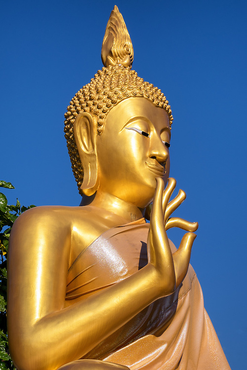 A Buddha statue and the local temple in Nakhon Nayok, Thailand