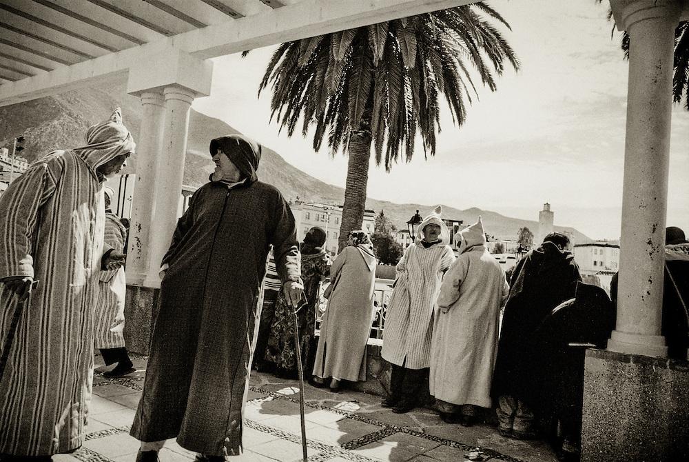198 / Männer in traditioneller Kleidung: AFRIKA, MAR, MAROKKO, CHEFCHAOUEN, Männer in traditioneller Kleidung unterhalten sich auf einem Platz in Chefchaouen. Chefchaouen, Chaouen oder Xauen ist eine marokkanische Stadt, die Hauptstadt der gleichnamigen Provinz. Sie befindet sich im Nordosten Marokkos, in den Auslaeufern des Rif-Gebirges, in der Naehe von Tetouan. - Marco del Pra / imagetrust - Stichworte: Afrika, Marokko, Maghreb, Maroc, Chefchaouen, Chaouen, Xaouen, Koenigreich, Koenig, Mohammed VI, Medina, Altstadt, Mann, Maenner, alt, alter, Islam, islamisch, Muslim, muslimisch, Arabisch, Berber, Sufi, Sufismus,  Religion, Schwarz, Weiss, Djellaba, Dschellaba, Galabiya, Rif, Gebirge, Tunica, Tradition, Kleidung, Gewand, Palme, Orient, Gehstock,