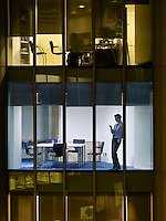 Business man text messaging in office view from building exterior