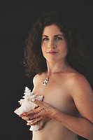Woman holding a seashell against her breast.