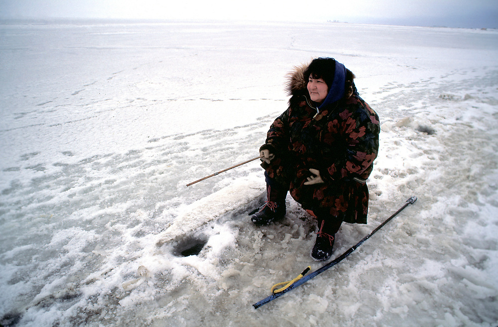 Barrow, Alaska, Native woman in a traditional kuspuk ice fishing through a hole in the frozen ice pack