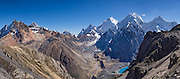 """Cordillera Huayhuash panorama from San Antonio Pass (5000 meters or 16,4000 feet) includes left to right: pyramidal Yerupaja Grande (center, 6635 m or 21,770 ft, highest peak in the Amazon basin); Nevado Serapo with Siula Grande (6344 m or 20,800 ft) rising behind; and Nevado Carnicero (5960 m). Below is turquoise lake Juraucocha at 4343 m. This photo is from Day 6 of our 9 days trekking in 2014 around the Cordillera Huayhuash in the Andes Mountains, Peru, South America. With a severely broken leg in 1985, climber Joe Simpson crawled for 3 days alone over 5 miles down this hazardous glacier back to his empty camp in the Sarapococha Valley (center). The gripping 2003 British docudrama """"Touching the Void"""" captures the account told in Joe's 1988 book, """"Touching the Void: The True Story of One Man's Miraculous Survival."""" After climbers Joe Simpson and Simon Yates scaled the treacherous Siula Grande, Joe broke his leg, and their descent became one of the most amazing survival stories in mountaineering history. This panorama was stitched from 8 overlapping photos."""