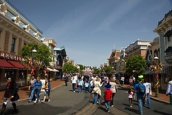 Crowds of tourists walk along Main Street, Disneyland with shops on either side, Disneyland Resort, Anaheim, California, United States of America