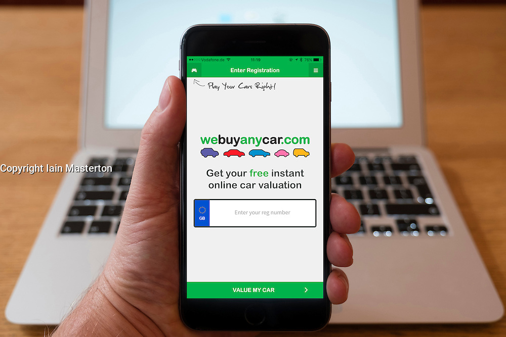 Using iPhone smartphone to display homepage form Webuyanycar.com e-commerce website