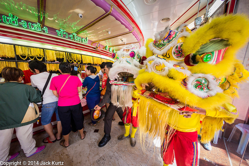 31 JANUARY 2014 - BANGKOK, THAILAND:   A Chinese Lion dance troupe performs in a jewelry shop on Yaowarat Road during Lunar New Year festivities, also know as Tet and Chinese New Year, in Bangkok. This year is the Year of the Horse. The Lion Dance scares away evil spirits and brings prosperity and luck. Ethnic Chinese make up about 14% of Thailand and Chinese holidays are widely celebrated in Thailand.     PHOTO BY JACK KURTZ