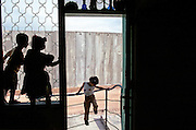 Palestinian children of the Armer family play in the window and the entrance of their home which has been isolated from their village of Masha in the Occupied West Bank Oct.28,2003.A 8 meter high concrete wall together with an electrical fence has cut this family off from their relatiand their village .Their  home is now on the Israeli side of the Wall.There home is adjascent to the Israeli Jewish settlement of ElkanaThe wall is part of a combination of fences, razor wires and trenches that Israel is building between Israel and the Palestinian territories Thursday Oct. 23, 2003. Israel says it is building it to keep out Palestinian suicide bombers and gunmen. The Palestinians say Israel is grabbing land, unilaterally drawing a border and making it impossible to establish a viable Palestinian state. (Photo by Heidi Levine/Sipa Press)