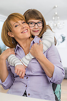 Portrait of affectionate daughter embracing mother at home