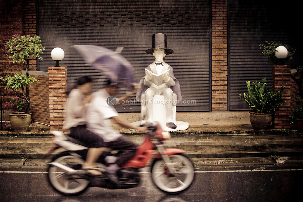 A couple riding a motorcycle in the rain holding an umbrella pass a statue of Abraham Lincoln on the sidewalk of Kata Noi Beach town, Phuket, Thailand.