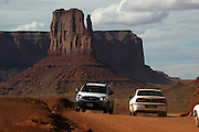 Traffic makes way through Monument Valley on the southern border of Utah with northern Arizona. Dust and pollution from cars is causing problems in the park. The valley lies within the range of the Navajo Nation Reservation. The Navajo name for the valley is Tsé Bii' Ndzisgaii - Valley of the Rocks.