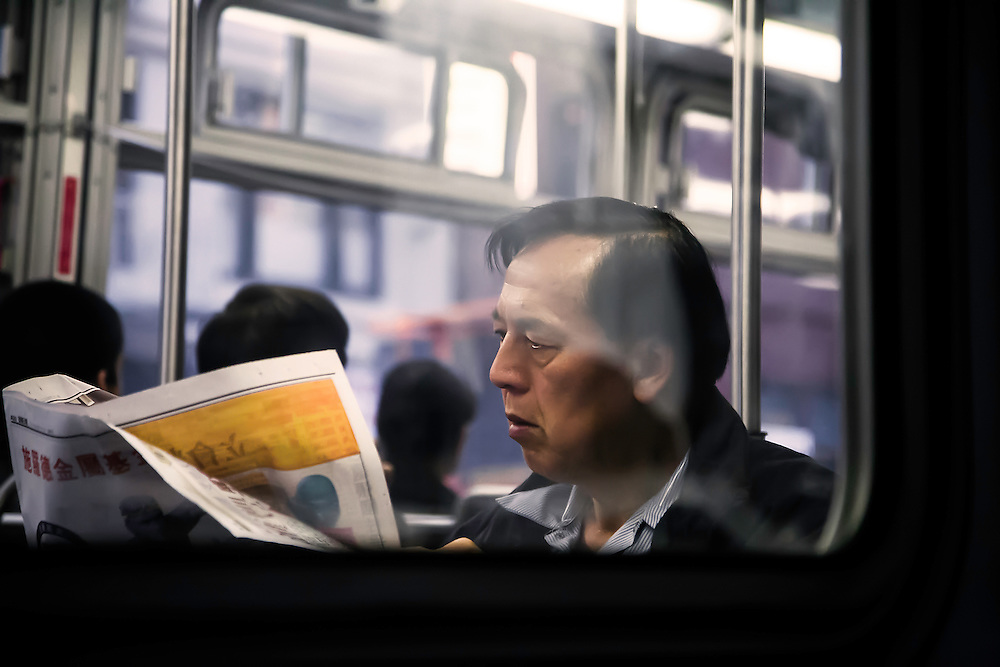 Man reads paper aboard city bus just outside Chinatown, in San Francisco, CA. Copyright 2008 Reid McNally.