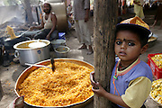 Preparing boondi in Ujjain, India, at one of the camps at the Kumbh Mela site. Every camp had its own large/small kitchen where food is prepared for people residing in that particular camp as well as outsiders who would walk in and out for lunch/dinner. Boondi can be a savory preparation or even sweet. A thin consistency dough is prepared using gram flour, water and spices. The man is pouring this dough through a big iron sieve which has holes in it so the dough falls in the form of drops in the hot oil and this is then fried. What comes out is the savory boondi. This boondi can be made sweet by putting in sugar syrup (prepared separately). (Supporting image from the project Hungry Planet: What the World Eats)