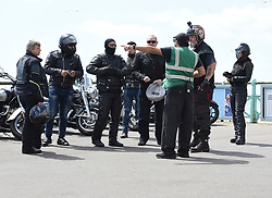 © Licensed to London News Pictures. 24/05/2020. Brighton, UK. A beach warden speaks to a group of bikers on Brighton seafront in East Sussex, during lockdown to prevent to spread of COVID-19.  Photo credit: Liz Pearce/LNP