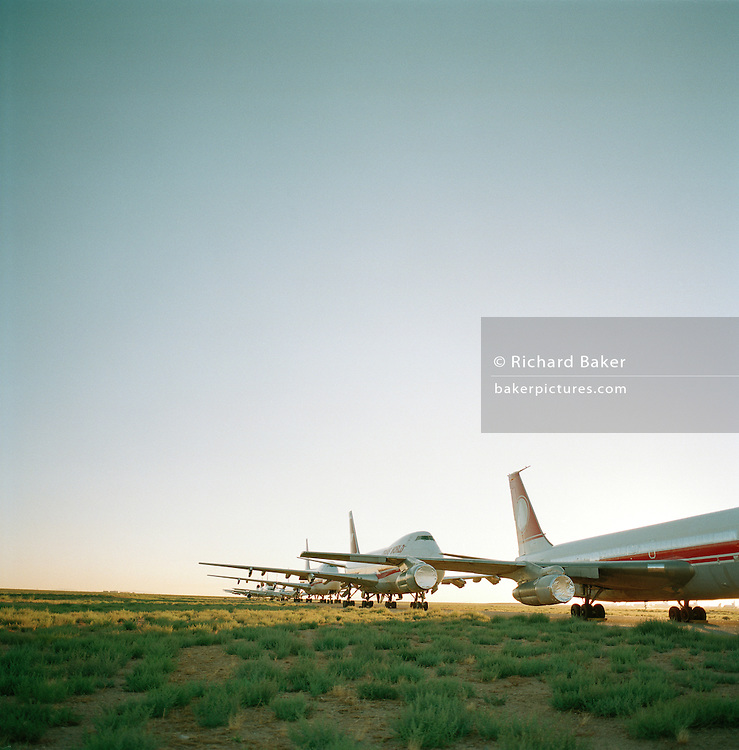 Stored old airliners sit in mid-day heat of arid Sonoran Desert at Mojave airport facility, awaiting recycling for scrap value.