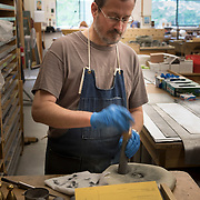 Theodore Stoddard tunes pipe parts for a pipe organ being built by C.b. Fisk, Inc,.